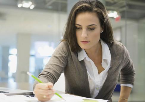 Una mujer de negocios concentrada trabaja con confianza en sus diseños.