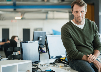 Un hombre mira pensativo la pantalla de su ordenador, pensando cuidadosamente la tarea que tiene entre manos.